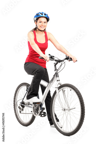 Female biker with helmet posing next to a bike