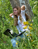 Young beautiful woman enjoys the nature workstation on meadow poster