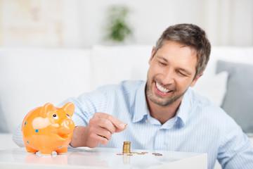 lächelnder mann stapelt münzen