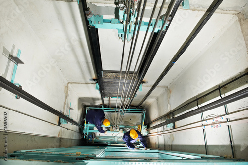 machinists adjusting lift in elevator hoistway - 41696502