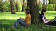 Two girls sitting in the park with laptops, tracking shot