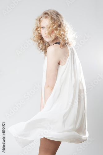 Young blonde girl posing in studio in white dress