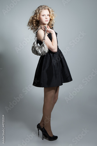Young blonde girl posing in studio