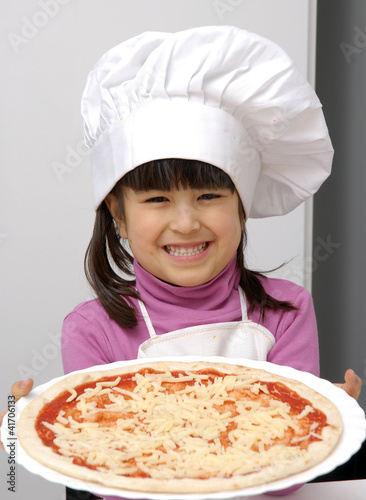 Niña chef sujetando una pizza,cocinando pizza.
