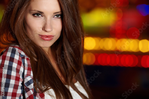 Portrait of beautiful petite woman in night city. Shallow DOF.