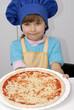 Niña chef sujetando una pizza,cocinando pizza.