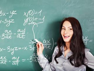 Schoolchild writing on blackboard.