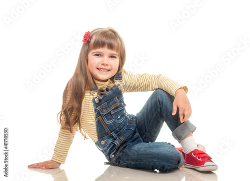 cute little girl wearing jeans overall sitting on the floor and