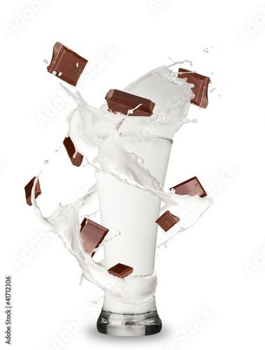 Leinwandbild Motiv Milk with chocolate bars splashing out of glass