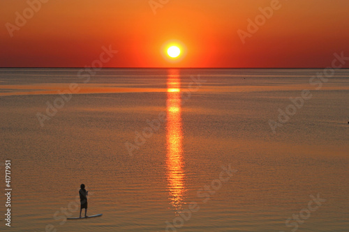 paddle boarder at sunset
