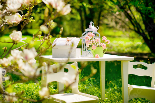 Table with chairs in a beautiful blooming garden