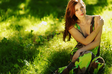 brunette sitting on green grass