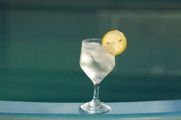 Swimming pool and a wine glass with ice and  lemon