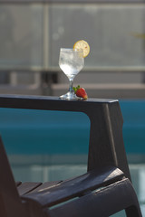 Swimming pool, lounge, a wine glass with ice, lemon and strawber
