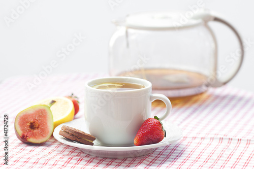 cup of tea,cookie, fig and strawberries on a plate