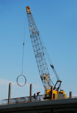 Iron workers moving rebar rings using a large crane poster