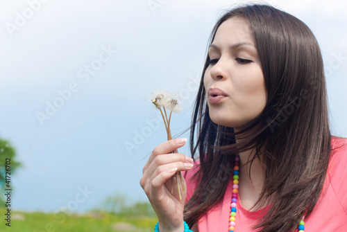 Woman blowing on dandelion
