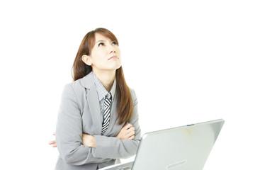 パソコンの前に座り悩んでいるオフィスレディー