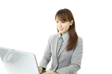 パソコンを使って仕事をする笑顔のオフィスレディー