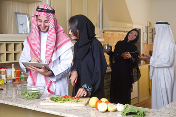 arabian couples gathering cooking & drinking coffee in kitchen