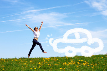 happy jumping girl with drawn car against blue sky