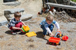 Two boy play outdoor with toys