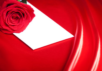 White envelope and red rose over abstract silk background