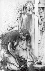 cemetery relief with angel and cross and crying woman figure wit