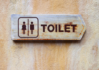 Ancient toilet sign on cement wall