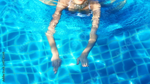 Pretty blond sexy woman is swimming in the pool