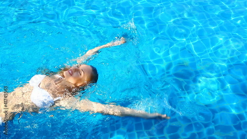 Adorable woman relaxing in swimming pool