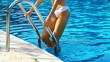 Sexy young woman climbing a swimming pool ladder