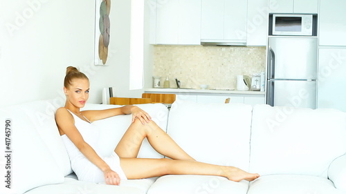 Sensual woman is sitting on white sofa in her modern home