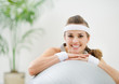 Portrait of smiling healthy woman on fitness ball