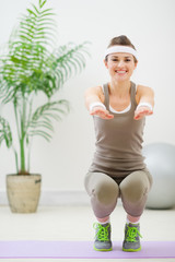 Smiling woman in sports wear squatting