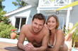 Happy young couple relaxing by pool