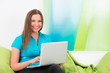 lachende junge frau sitzt mit laptop auf dem sofa