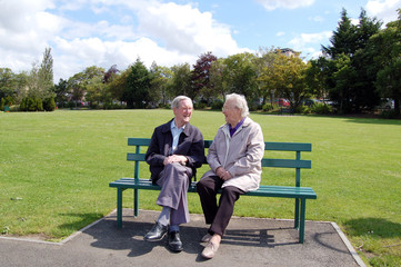 Senior couple chatting on a park bench