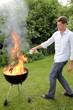 Mann mit Feuer beim Grillen