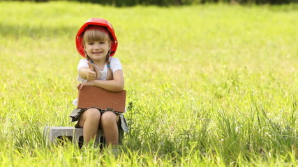 Little girl in the construction helmet sits on cinder block