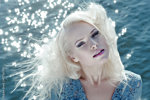Portrait of beautiful young woman against water