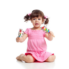 Baby  girl playing  with musical toys. Isolated on white backgro