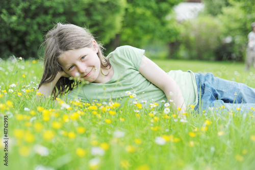 Mädchen liegt auf einer Wiese