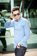 handsome man posing outdoors in blue shirt and sunglasses