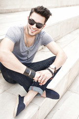 handsome male fashion model smiling, dressed casual - outdoor