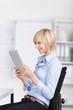 junge frau liest auf tablet im büro