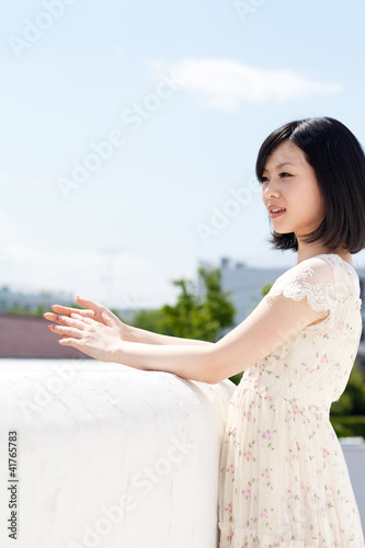 Beautiful young woman outdoors over blue sky