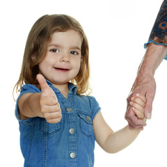 Little girl shows thumb up taking the hand of her grandmother