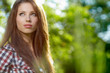 beautiful young brunette woman standing near garden
