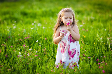 Sweet blonde girl smelling flowers on the meadow